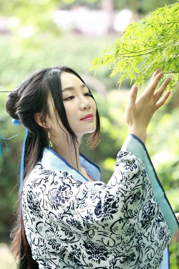 Azjatycka Chińska kobieta w tradycyjnej Błękitnej i białej Hanfu sukni, sztuka w sławnym ogródzie, stojak pod klonowym drzewem obrazy royalty free