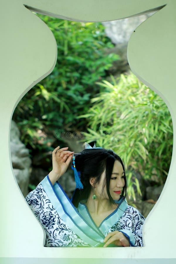 Azjatycka Chińska kobieta w tradycyjnej Błękitnej i białej Hanfu sukni, sztuka w sławnym ogródzie, stojak przed okno fotografia stock