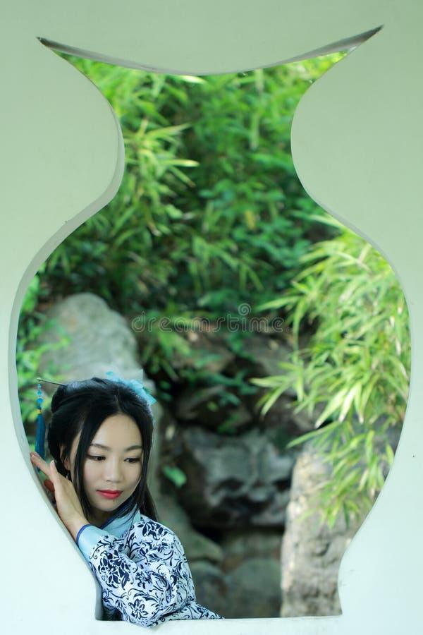 Azjatycka Chińska kobieta w tradycyjnej Błękitnej i białej Hanfu sukni, sztuka w sławnym ogródzie, stojak przed okno fotografia royalty free
