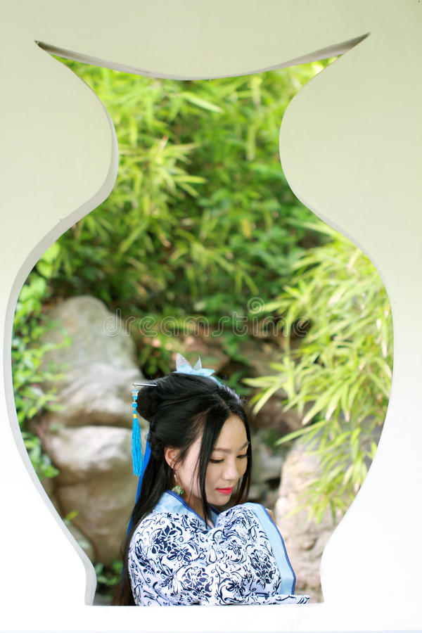 Azjatycka Chińska kobieta w tradycyjnej Błękitnej i białej Hanfu sukni, sztuka w sławnym ogródzie, stojak przed okno obraz stock