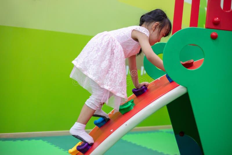 Azjatycka Chińska mała dziewczynka bawić się przy mini rockowego pięcia ścianą obraz stock