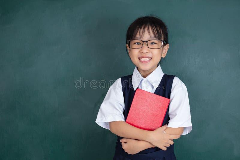 Azjatycka Chińska mała dziewczynka w jednolitej pozycji przeciw zielonemu blac obraz royalty free