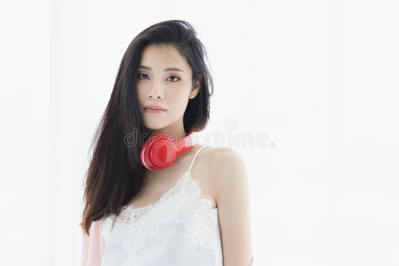 Azjatycka czarni w?osy kobieta jest ubranym czerwonego he?mofon zdjęcia stock