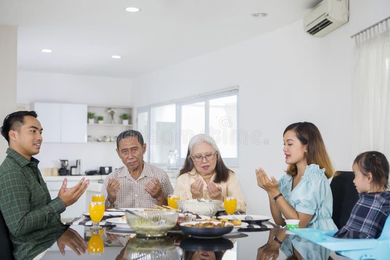 Azjatycka dalsza rodzina ono modli się wpólnie przed posiłkami obraz royalty free