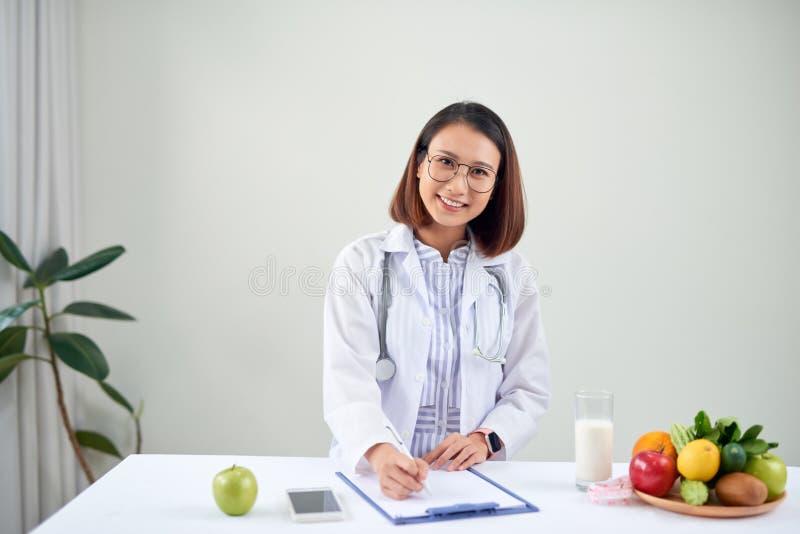 Azjatycka dietetyka z owocami pracującymi przy biurku Koncepcja opieki zdrowotnej i diety zdjęcie royalty free