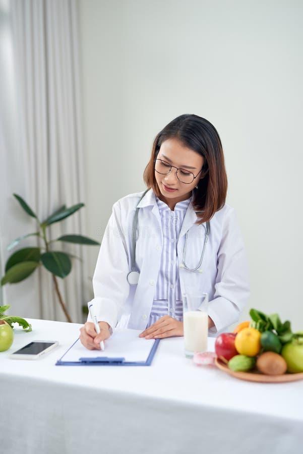 Azjatycka dietetyka z owocami pracującymi przy biurku Koncepcja opieki zdrowotnej i diety obraz royalty free