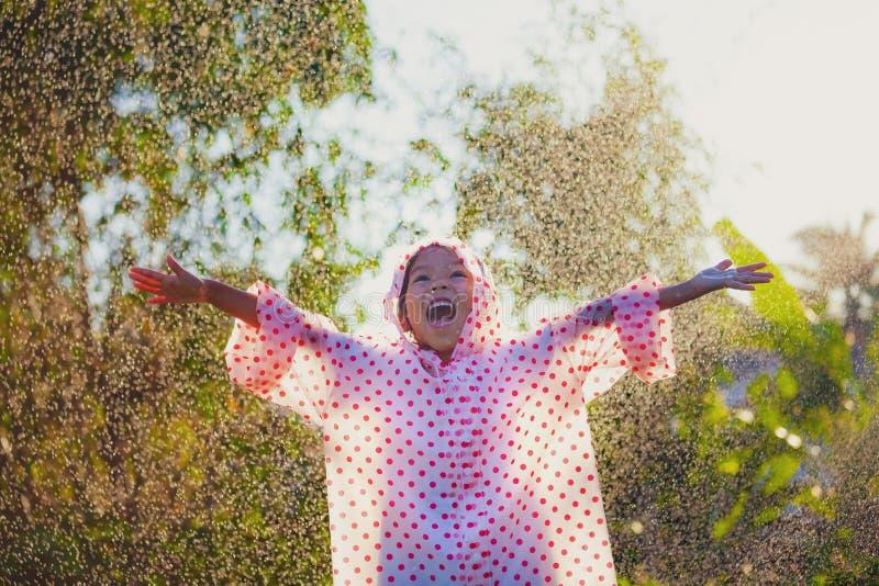 Azjatycka dziecko dziewczyna jest ubranym deszczowa ma zabawę bawić się z deszczem w świetle słonecznym obraz stock
