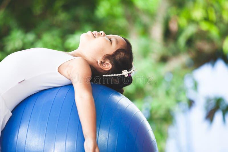 Azjatycka dziecko dziewczyna robi rozciągania ćwiczeniu na sprawności fizycznej piłce zdjęcia royalty free