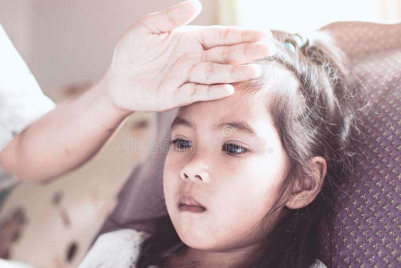 Azjatycka dziecko dziewczyny choroba i matki ręka dotykamy jej czoło obraz royalty free