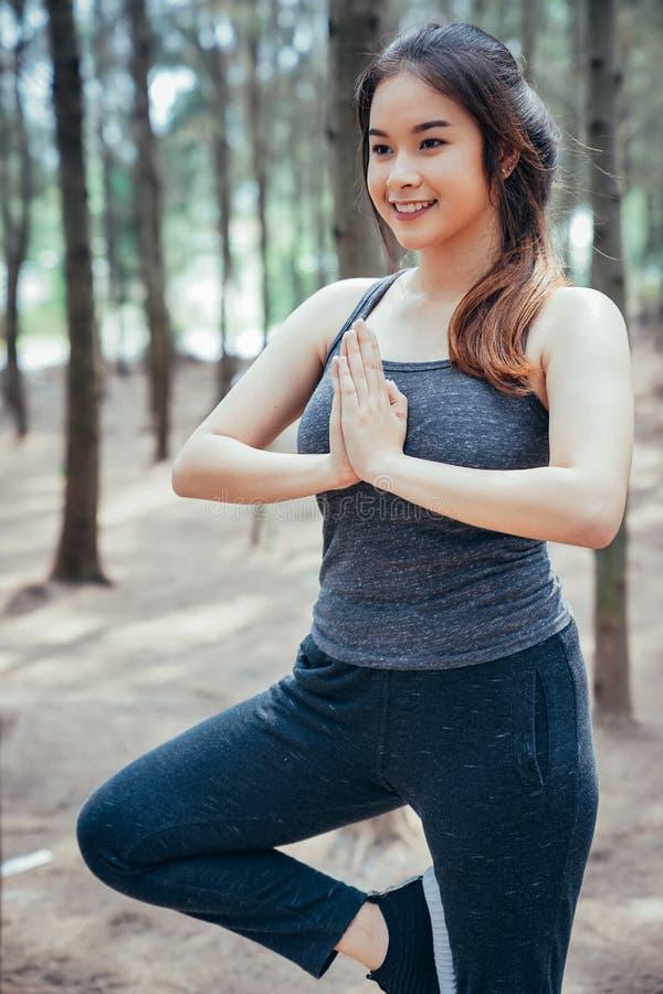 Azjatycka dziewczyna ćwiczy w weekend w sosnowym lesie zdjęcie stock