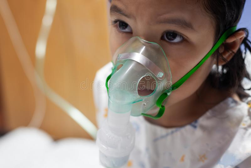 Azjatycka dziewczyna astmy, zapalenie płuc potrzeby lub choroby nebulization obok dostawać inhalator maskę na jej twarzy i zdjęcia royalty free