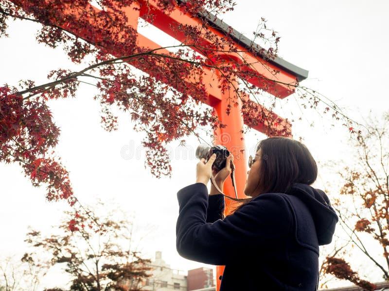 Azjatycka dziewczyna bierze fotografię z czerwonym liściem klonowym z światłem słonecznym i miękką częścią zdjęcia royalty free