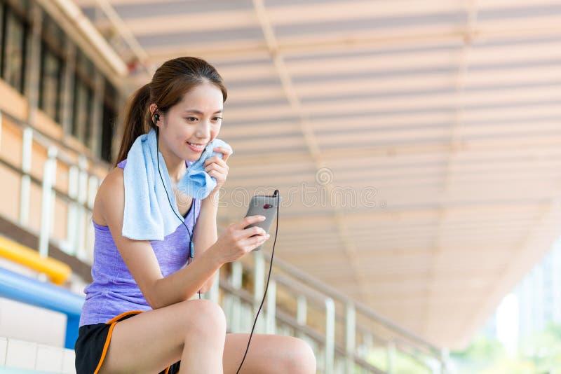 Azjatycka dziewczyna bierze przerwę i słucha muzyka i obsiadanie na sporcie obraz royalty free