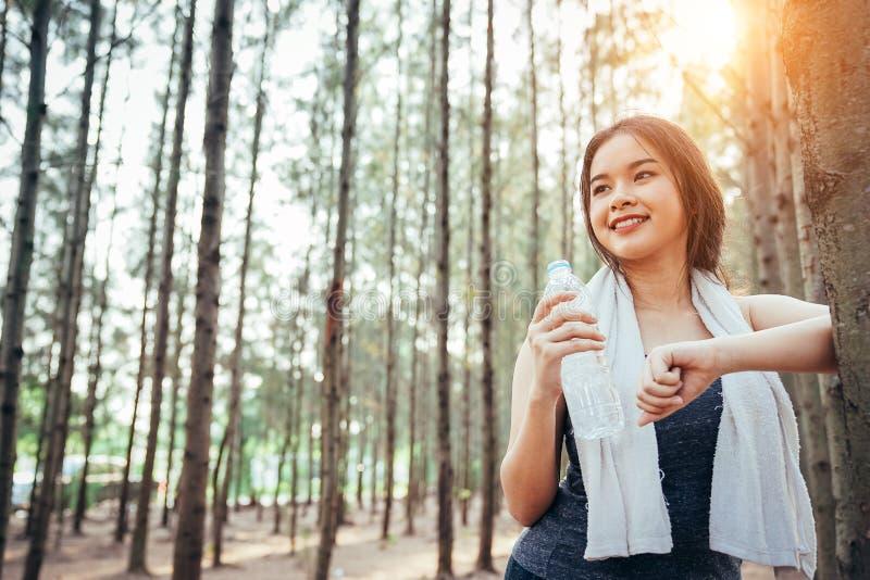 Azjatycka dziewczyna jest ćwicząca chłodno wodę i pijąca obraz royalty free