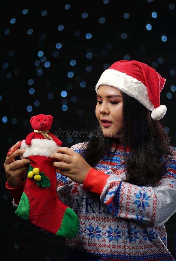 Azjatycka dziewczyna Jest ubranym Bożenarodzeniowego pulower Kapeluszowy Trzyma Chris i Santa fotografia royalty free