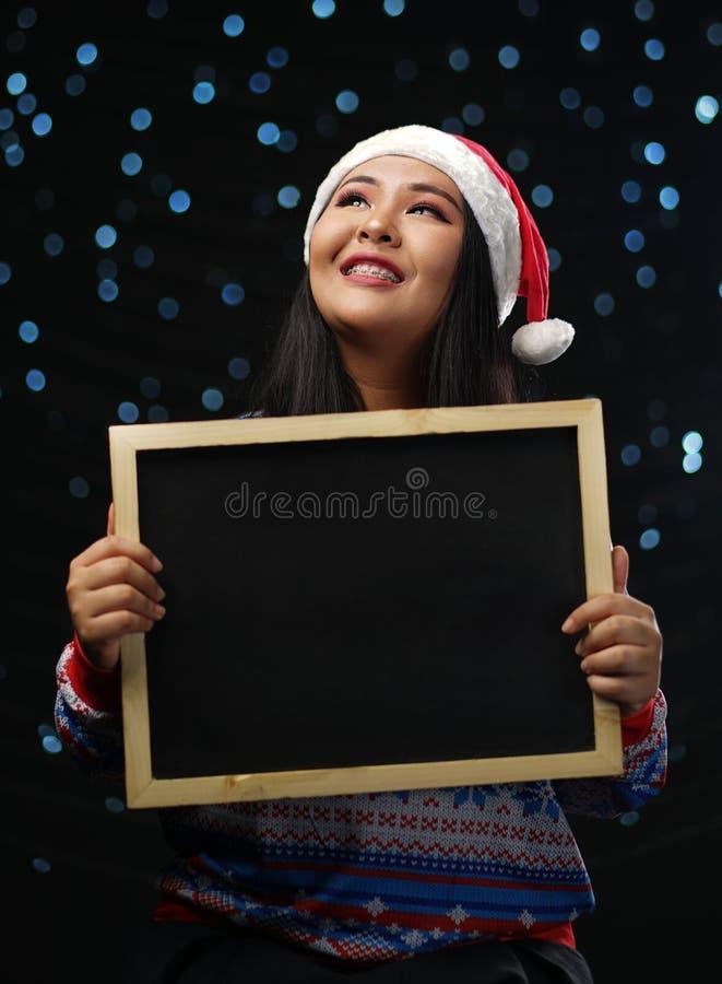 Azjatycka dziewczyna Jest ubranym Bożenarodzeniowego puloweru i Santa mienia Kapeluszowego czerń zdjęcia royalty free