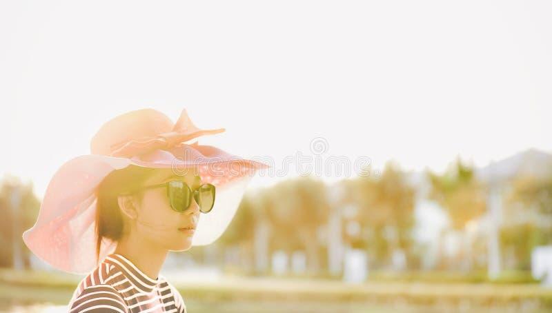 Azjatycka dziewczyna jest ubranym kapelusz i szkła podczas gdy być na wakacjach w sumie zdjęcie stock