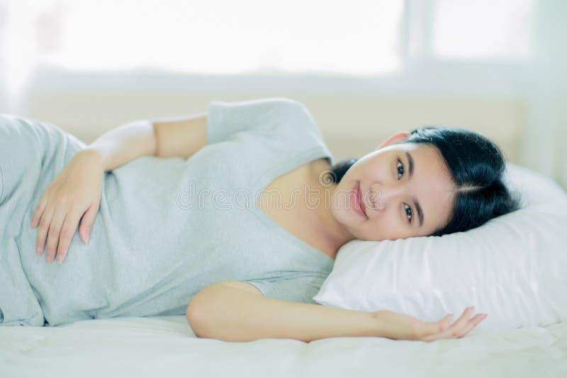 Azjatycka dziewczyna kłaść puszek na łóżku fotografia stock