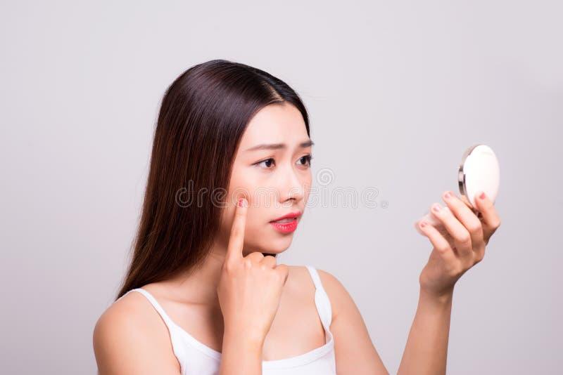 Azjatycka dziewczyna która sprawdza jej skórę, skóry opieka, trądzika traktowanie zdjęcie stock