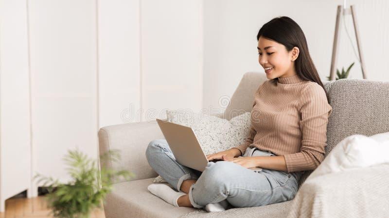 Azjatycka dziewczyna Pracuje na laptopie Online, Używać internet zdjęcia stock