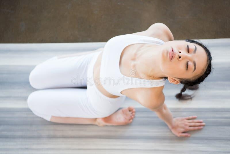Azjatycka dziewczyna robi joga w zacofanej chylenie pozie z oczami zamykającymi fotografia stock