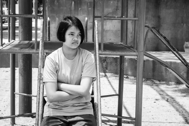 Azjatycka dziewczyna siedzi samotny czarny i biały fotografia stock