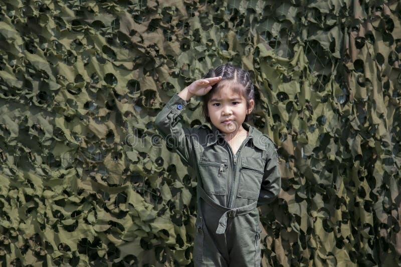 Azjatycka dziewczyna szacuneku żołnierza akcja z zieloną żołnierza lub pilota un zdjęcie royalty free