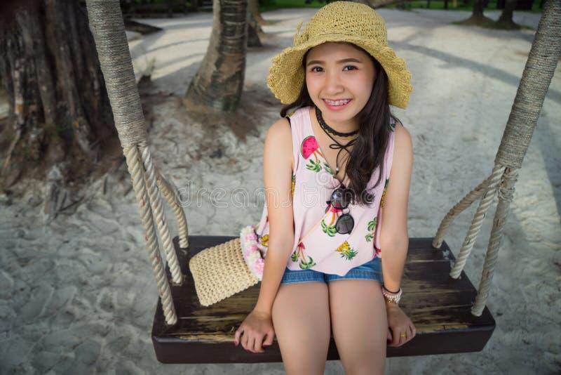 Azjatycka dziewczyna uśmiecha się zabawę na wakacje i ma z słomianym kapeluszem obrazy royalty free