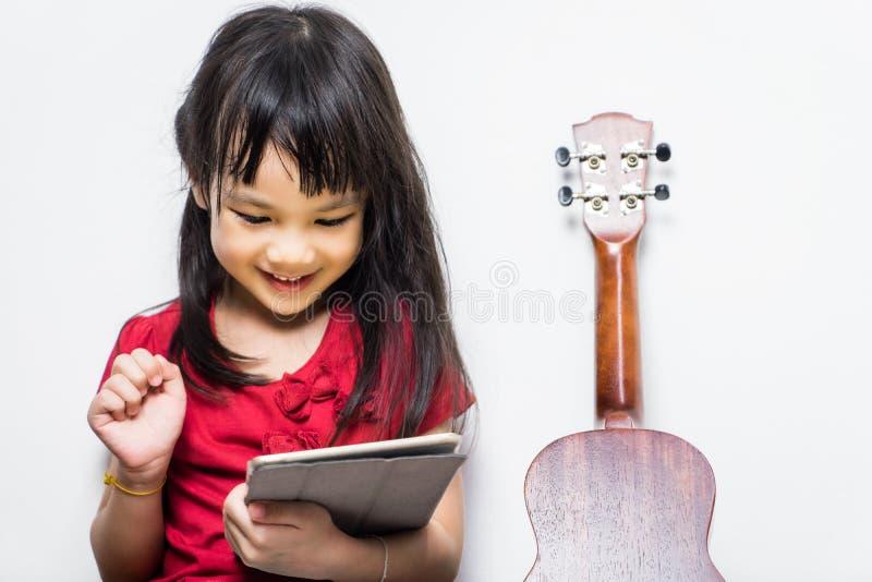 Azjatycka dziewczyna używa jej pastylkę uczyć się bawić się muzykę fotografia royalty free