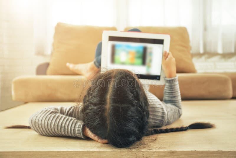 Azjatycka dziewczyna używa pastylkę, wczesną edukację i uczyć się, obraz royalty free