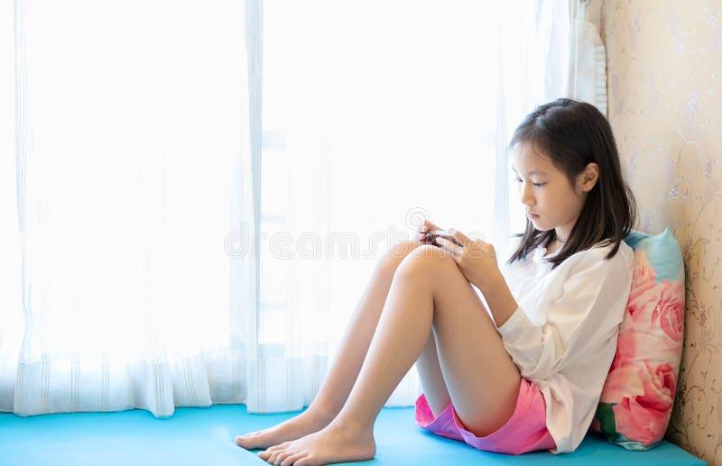 Azjatycka dziewczyna używa smartphone blisko okno w sypialni w domu, technologii i komunikacji, pojęcie obraz royalty free