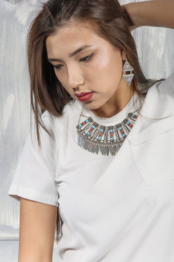 Azjatycka dziewczyna ubierał w białej koszula błękitnych spodniach i obraz royalty free