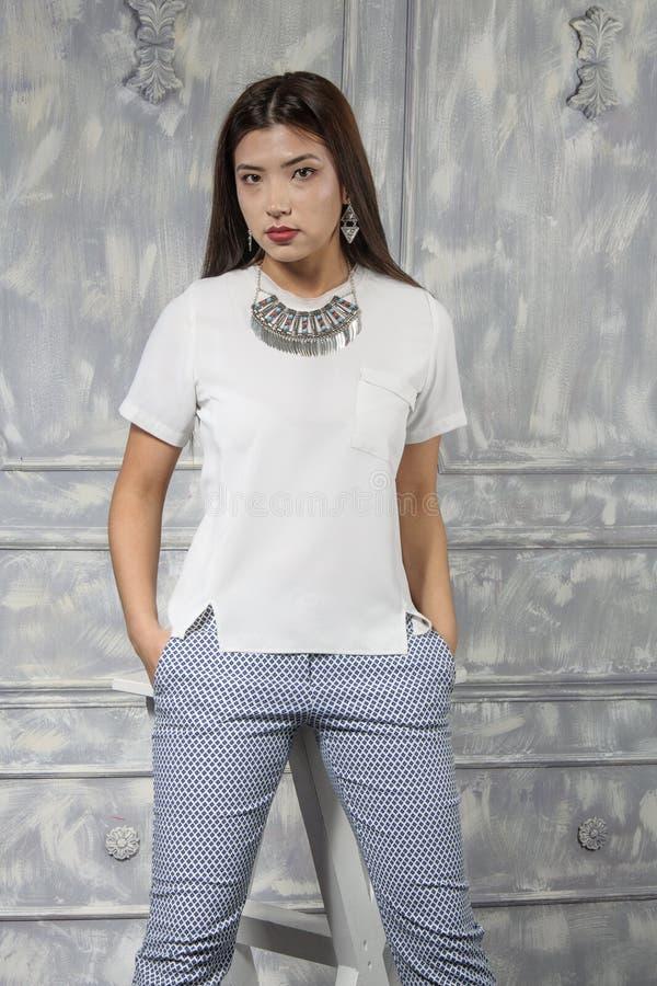 Azjatycka dziewczyna ubierał w białej koszula błękitnych spodniach i fotografia royalty free