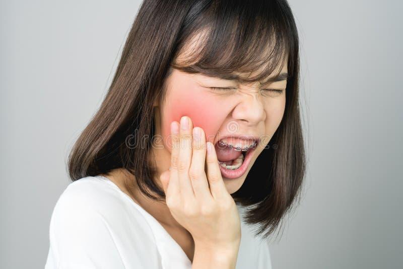 Azjatycka dziewczyna w białej przypadkowej sukni Pokazuje daleko toothache przez no utrzymywać dobrych oralnych zdrowie, Być może fotografia royalty free