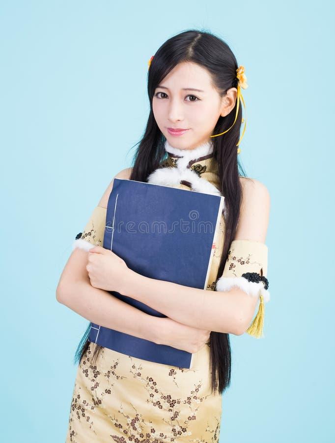 Azjatycka dziewczyna w cheongsam qipao z chińską książką zdjęcia royalty free