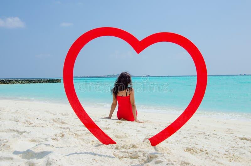 Azjatycka dziewczyna w czerwonym smokingowym obsiadaniu z powrotem kamera przy tropikalnej plaży inside sercem obraz royalty free