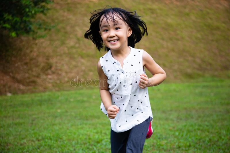 Azjatycka dziewczynka biegajÄ…ca szczęśliwie zdjęcia stock