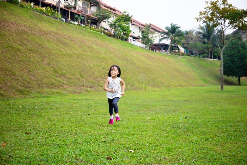 Azjatycka dziewczynka biegająca szczęśliwie obrazy royalty free