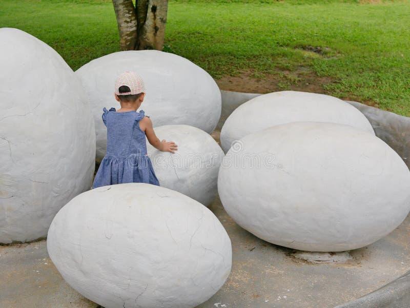 Azjatycka dziewczynka dotyka dinosaura jajko badać jeżeli czuje cokolwiek inside obraz stock
