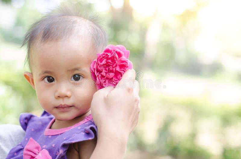Azjatycka dziewczynka z menchii róży kwiatem w jej włosy na lekkim natura fotografia royalty free