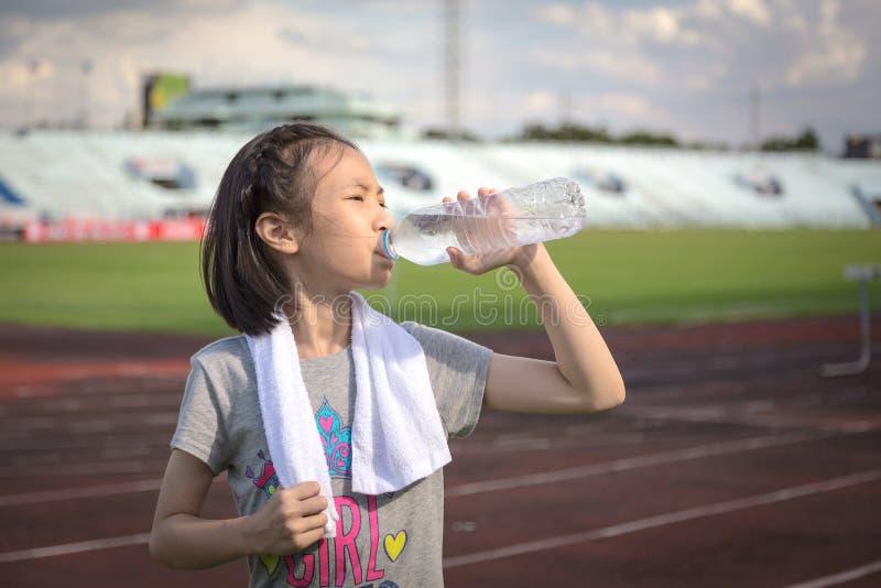 Azjatycka dziewczyny woda pitna od klingeryt butelek po jogging, mała dziewczynka napoju spragniona wodna opłata gorąca pogoda po obraz royalty free