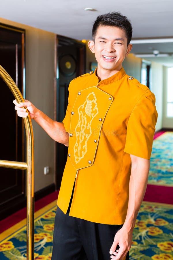 Azjatycka dzwonkowej chłopiec lub furtianu dowiezienia walizka pokój hotelowy zdjęcia royalty free