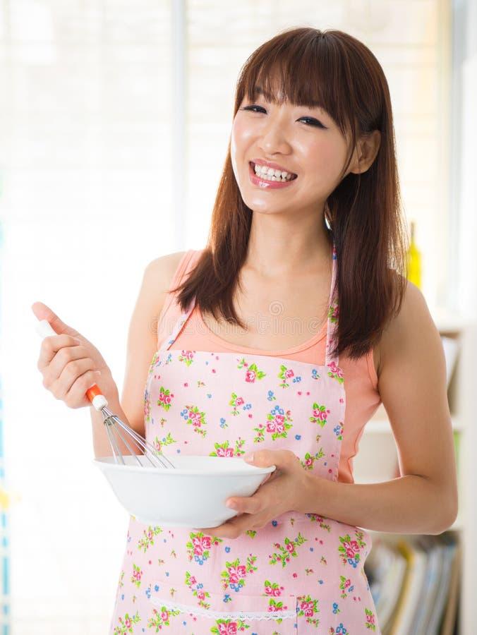 Azjatycka kobieta cieszy się pieczenie zdjęcia stock