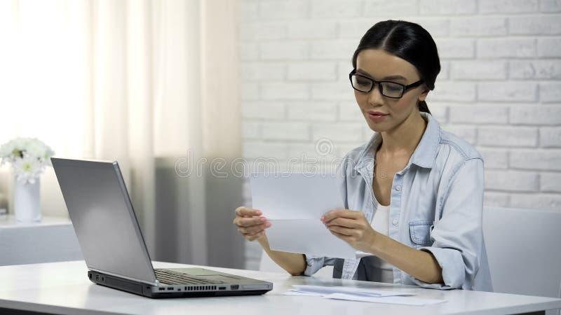 Azjatycka kobieta czyta list w szkłach, wezwanie do sądu, kwit korespondencja obrazy royalty free