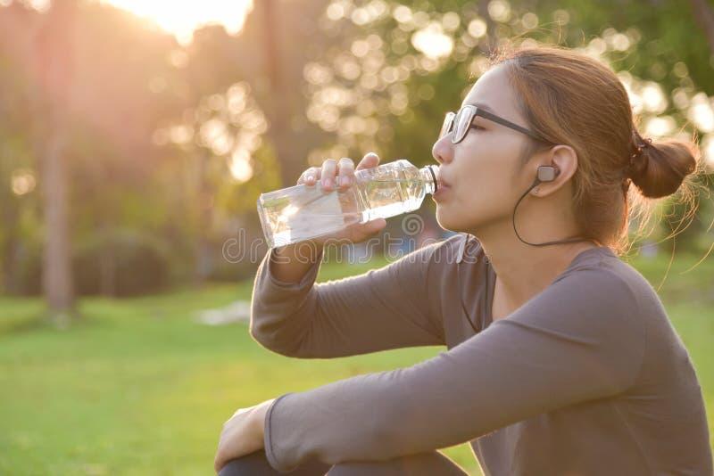 Azjatycka kobieta jest odpoczynkowa i wodo pitna obraz royalty free