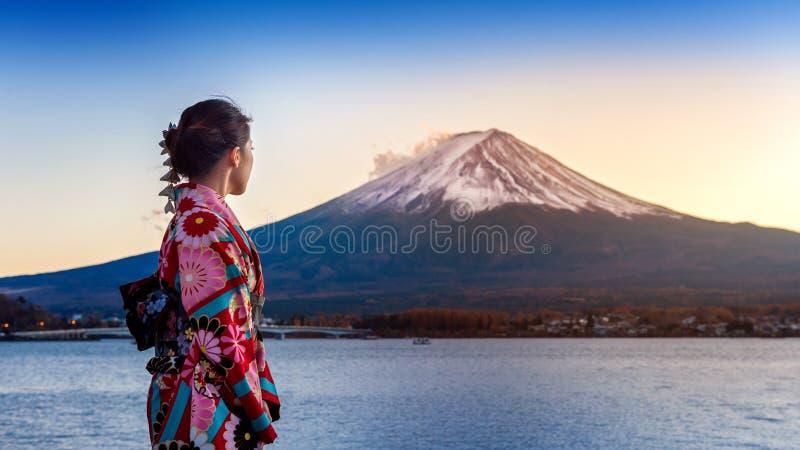 Azjatycka kobieta jest ubranym japońskiego tradycyjnego kimono przy Fuji górą Zmierzch przy Kawaguchiko jeziorem w Japonia obraz royalty free