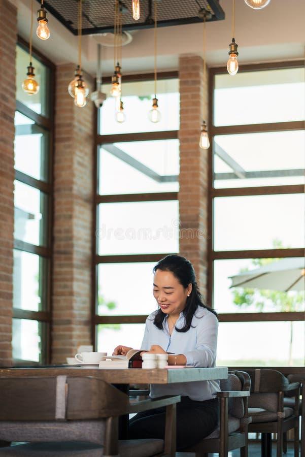Azjatycka kobieta ma kaw? i czytanie w barze zdjęcie royalty free