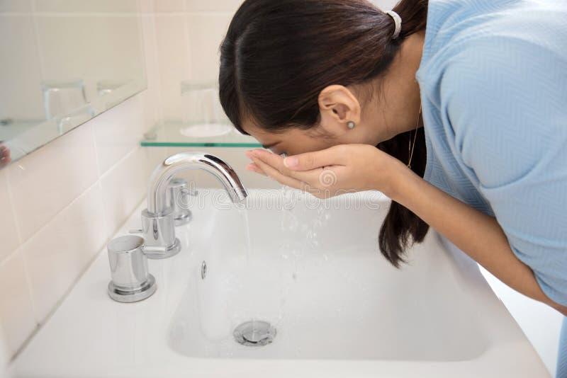 Azjatycka kobieta myje jej twarz na zlew zdjęcie stock