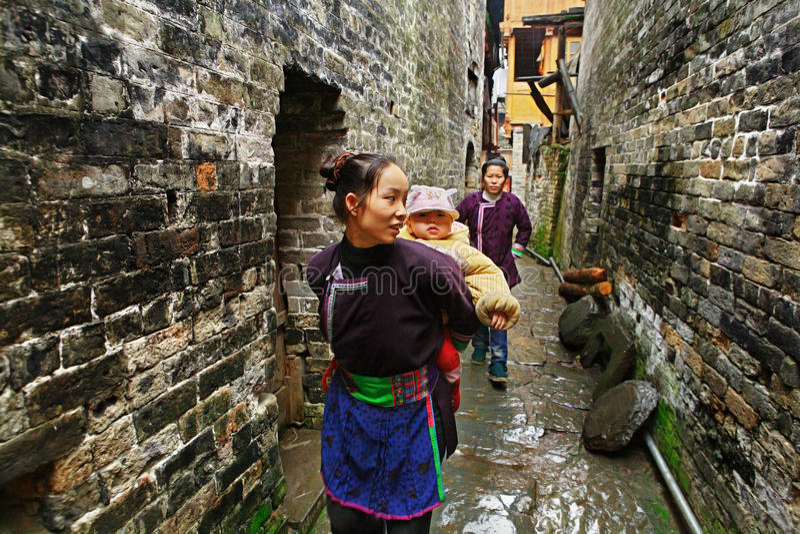 Azjatycka kobieta niesie dziecka za plecy w wiejskim Chiny. zdjęcia royalty free