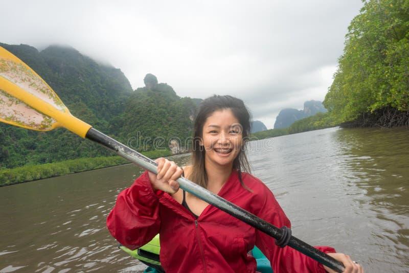 Azjatycka kobieta ono uśmiecha się na kajaku z halnym tłem obraz royalty free